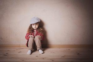 sad child sitting on the floor in room